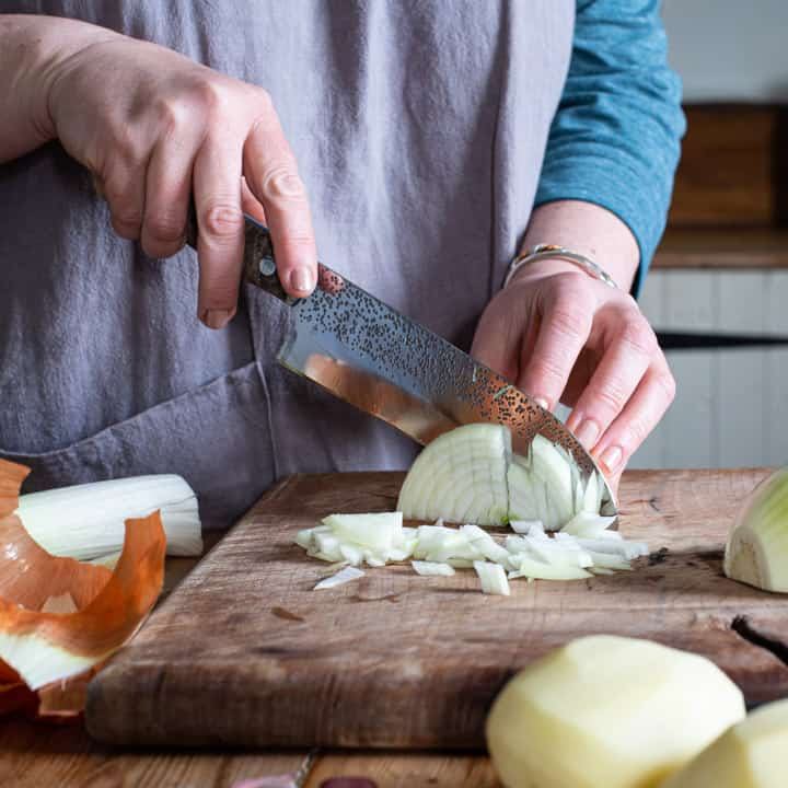 womans hands chopping an onion finely on a wooden chopping board
