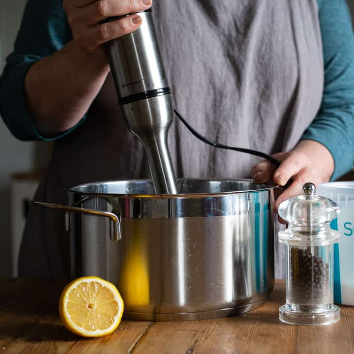 womans hands holding an immersion blender over a large silver pan with half a lemon and a pepper mill in front