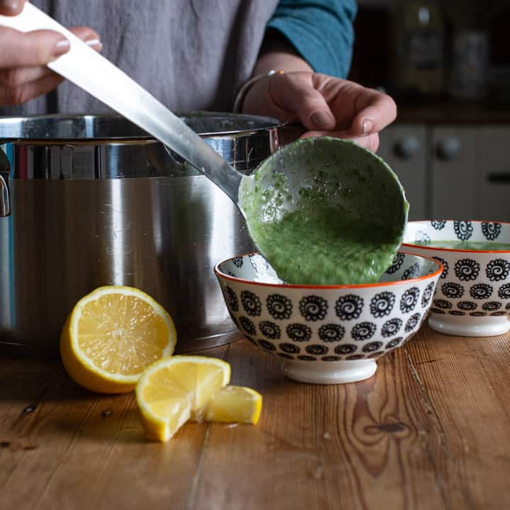 womans hands spooning bright green soup into smal white bowls with a silver ladle on a wooden kitchen counter