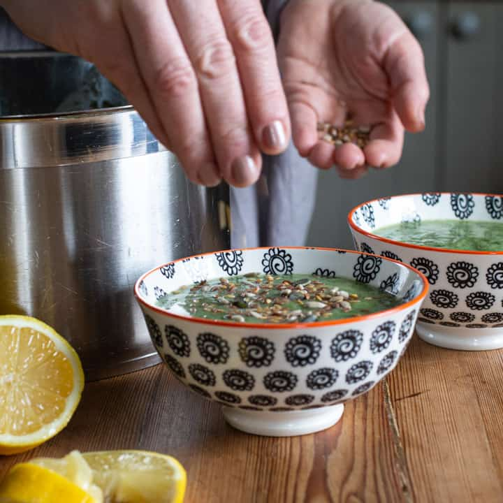 woman sprinkling mixed seeds onto a bowl of bright green soup next to lemon slices and a silver saucepan