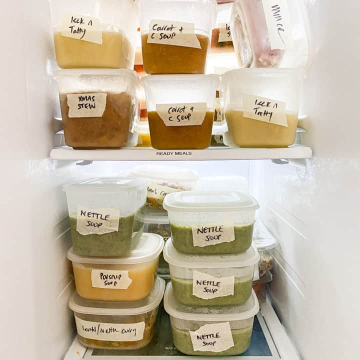 white freezer contents with various homemade soups and meal stacked in tupperware containers and all labelled with their contents