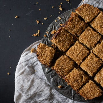 black background with cream linen and plate of oat and date flapjacks