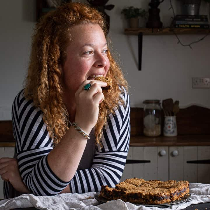 woman with red hair in stripey top leaning on wooden kitchen counter eating fresh date flapjack