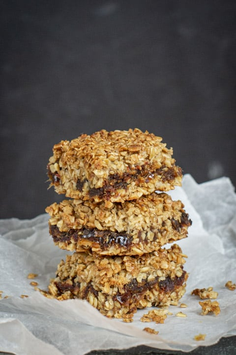 Three date flapjacks piled on top of each other on baking paper