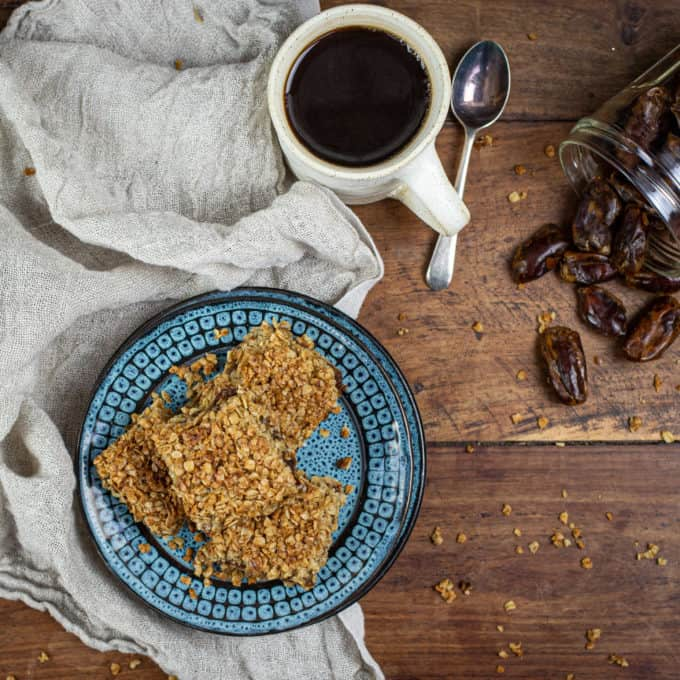 Ariel view of plate of flapjacks, cup of coffee, teaspoon and dates in a jar on a wooden table