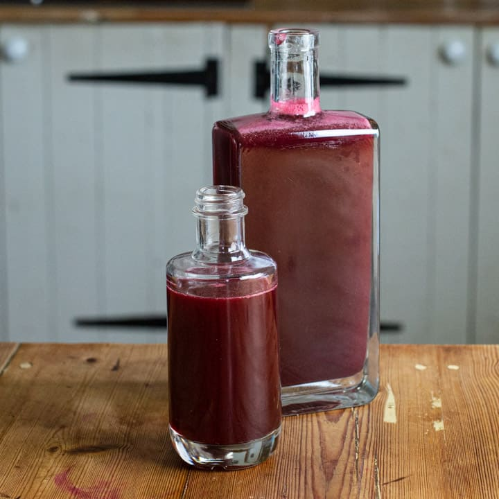 2 glass bottles on a rustic wooden counter filled with homemade blackcurrant syrup