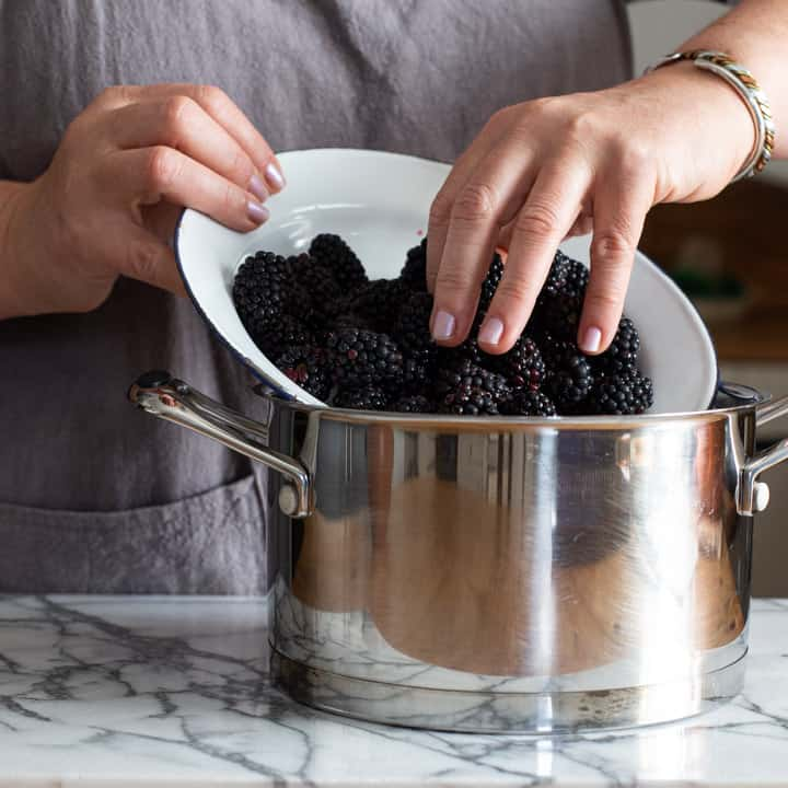 womans ahnds tipping fresh blackberries from a white bowl into a silver saucepan