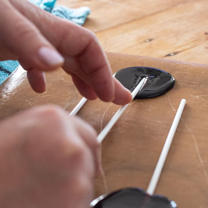 womans hands pushing a white paper lollipop stick into a circle of hot blackberry candy on a brown baking sheet