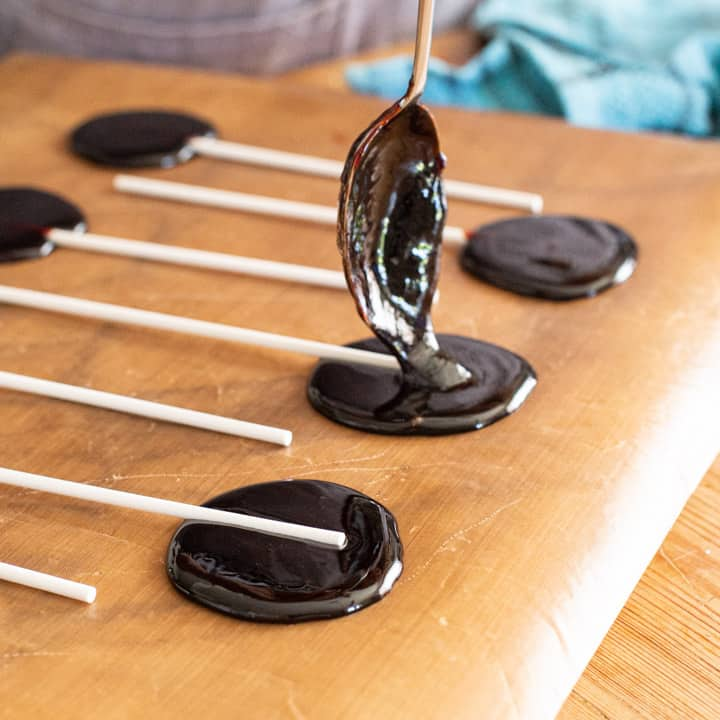 a teaspoon of blackberry candy syrup being poured over a white paper lollipop stick