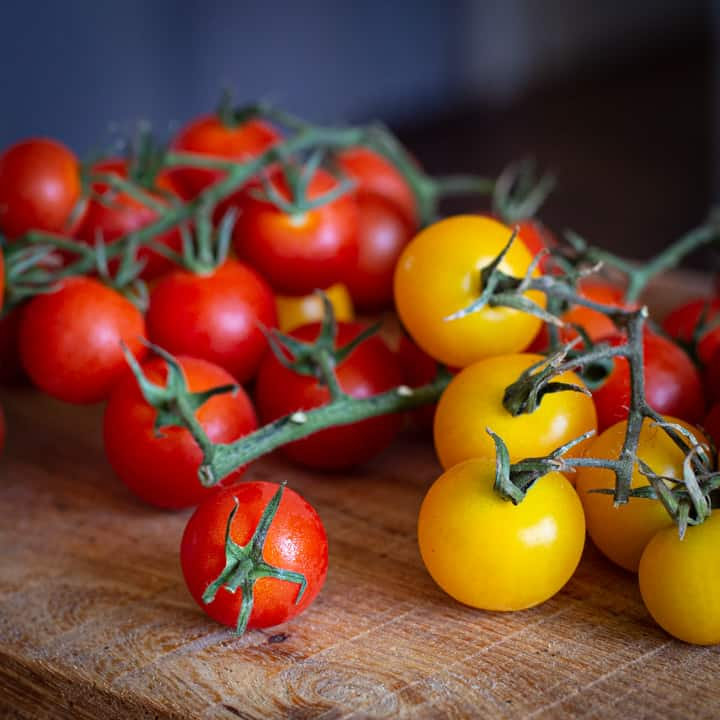 red and yellow cherry tomatoes on a wooden board