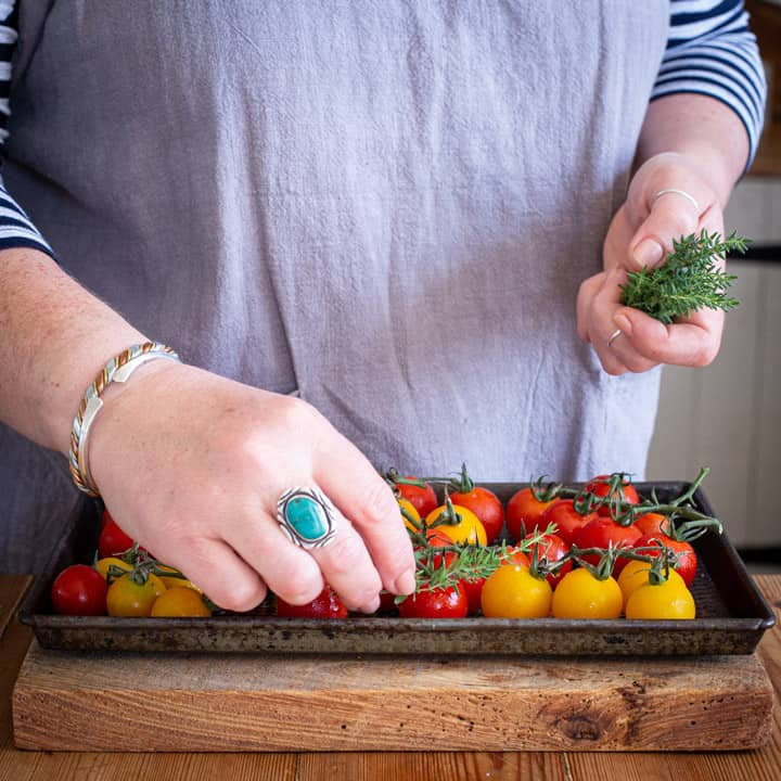 womans hands placing fresh herbs on a tray of red and yellow cherry tomatoes for roasting