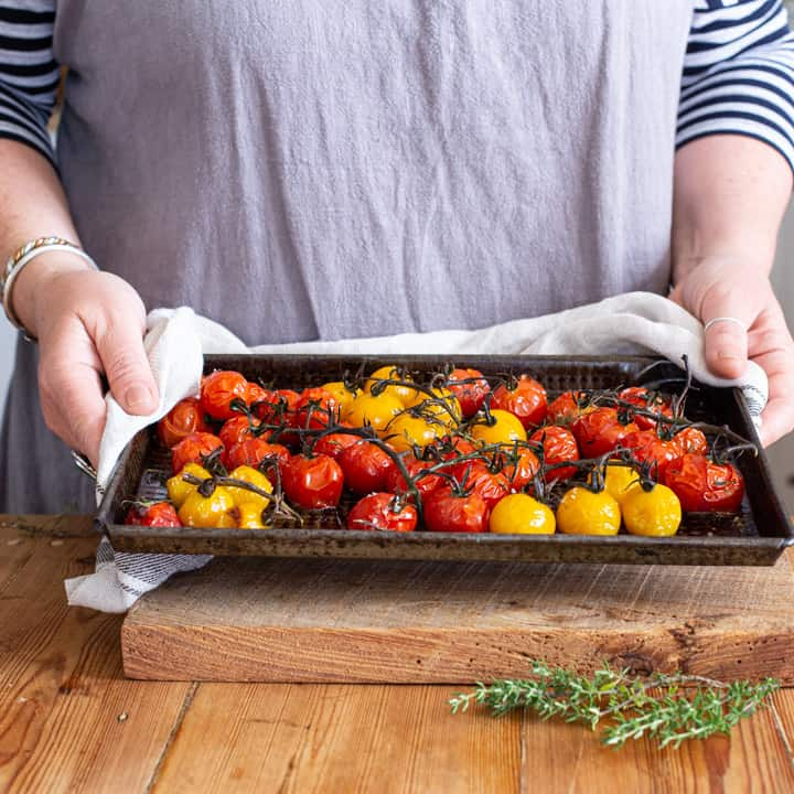womans hands holding black tray of roasted red and yellow cherry tomatoes