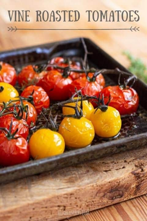roasted red and yellow cherry tomatoes in a black baking tray on a wooden board