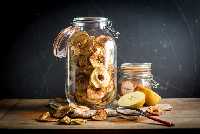 Glass jar filled with dried apple rings that have been dusted with cinnamon