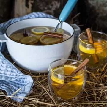 Two full glasses and a pan of mulled cider on straw bale