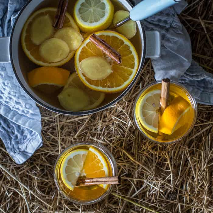 Two full glasses and a pan of hot Mulled scrumpy cider on straw bale