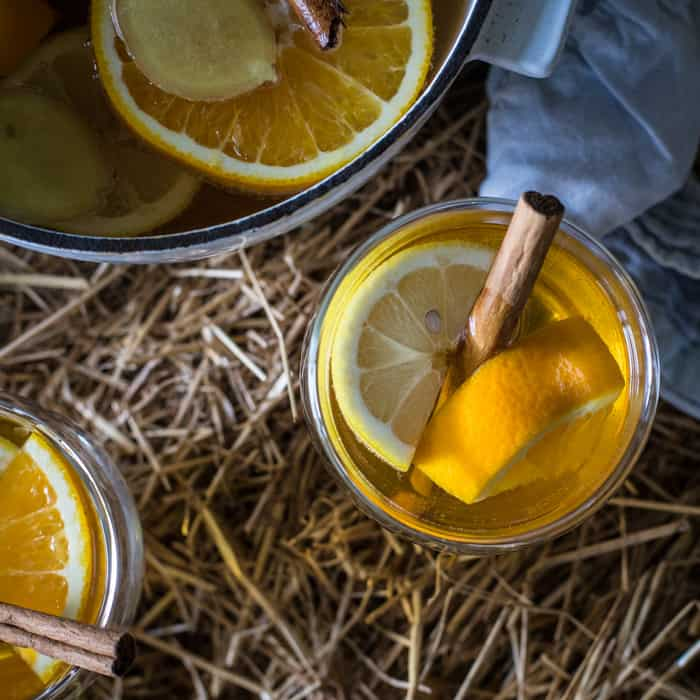 Two full glasses and a pan of mulled cider on straw bale with slices of lemon and cinnamon sticks