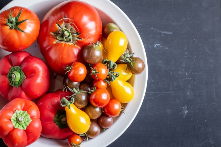 black background with white bowl full of fresh yellow, orange and red tomatoes