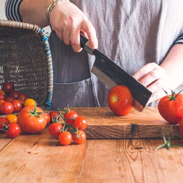 womans hands slicing red tomato on wooden chopping board