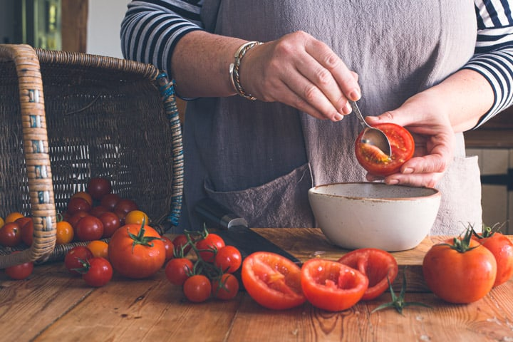 womans hands scooping seeds out of red tomato on wooden chopping board