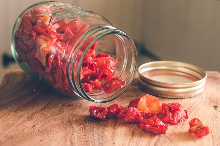 glass jar on wooden kitchen counter filled with dried cherry tomatoes