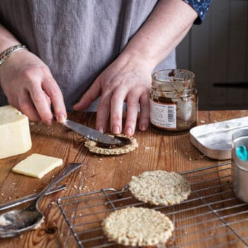 womans hands on wooden kitchen bench spreading fresh hot oatcakes with chutney surrounded by baking mess and cheddar cheese