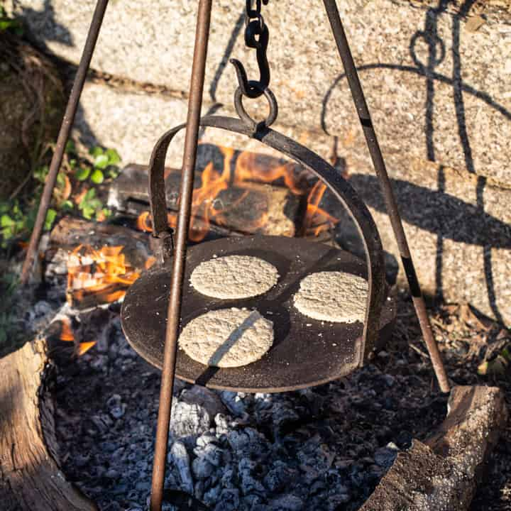 cast iron griddle hanging from a hook over a campfire with 3 homemade oatcakes cooking on the hot plate