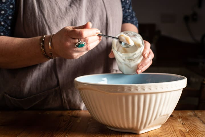 womans hands spooning lard from a glass jar into a white mixing bowl of oatcake ingredients