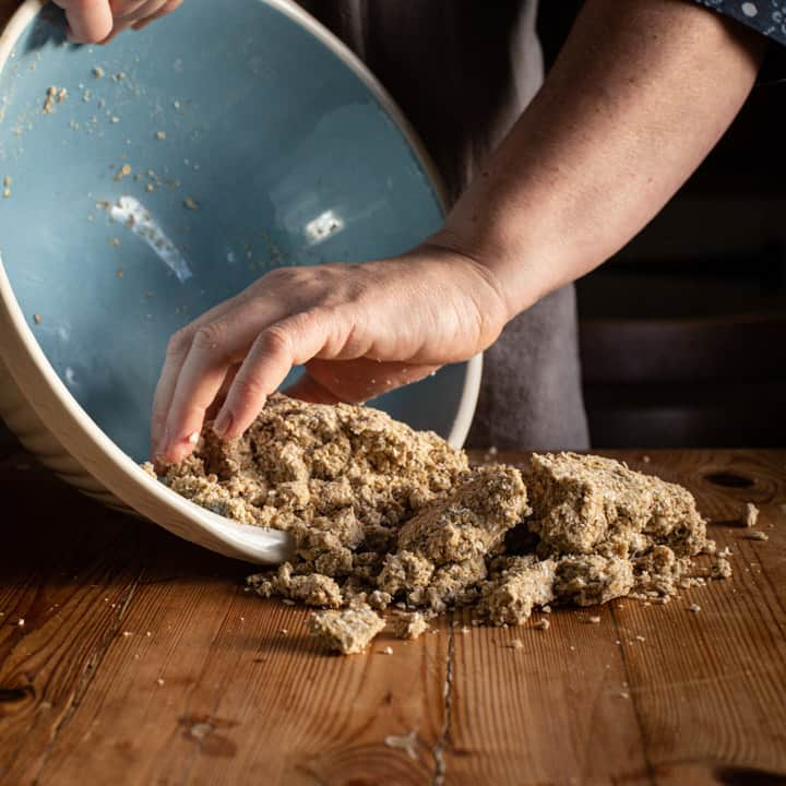 womans hands tipping crumbly oatcake dough from a blue and white bowl onto a wooden kitchen counter