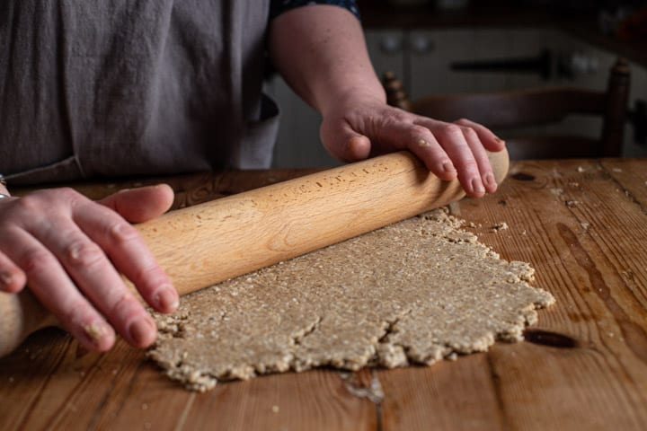 womans hands rolling out oatcake dough on a wooden counter