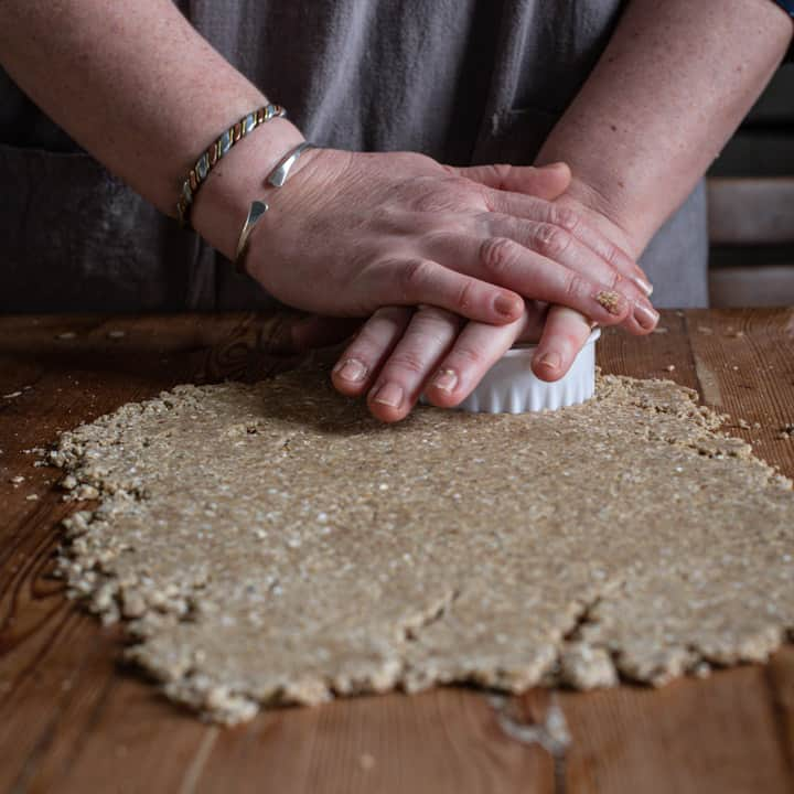 womans hands cutting oatcake dough with a white cookie cutter on a wooden counter