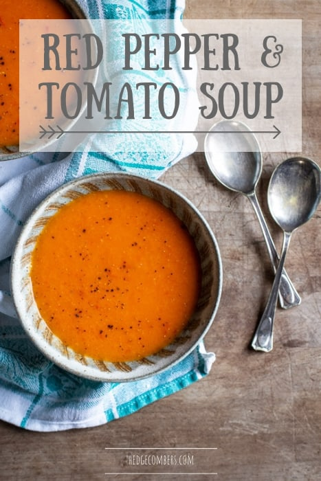 wooden backgrouns with 2 bowls of red pepper tomato soup on a blue and white cloth with 2 spoons