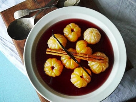 white bowl on wooden background with poached satsumas in red wine, cinnamon stick and vanilla pod