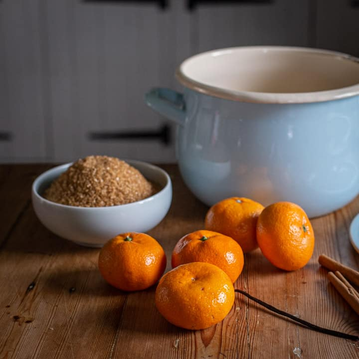 rustic kitchen country with a pale blue enamel pan, satsumas, brown sugar in a pale blue bowl and cinnamon sticks