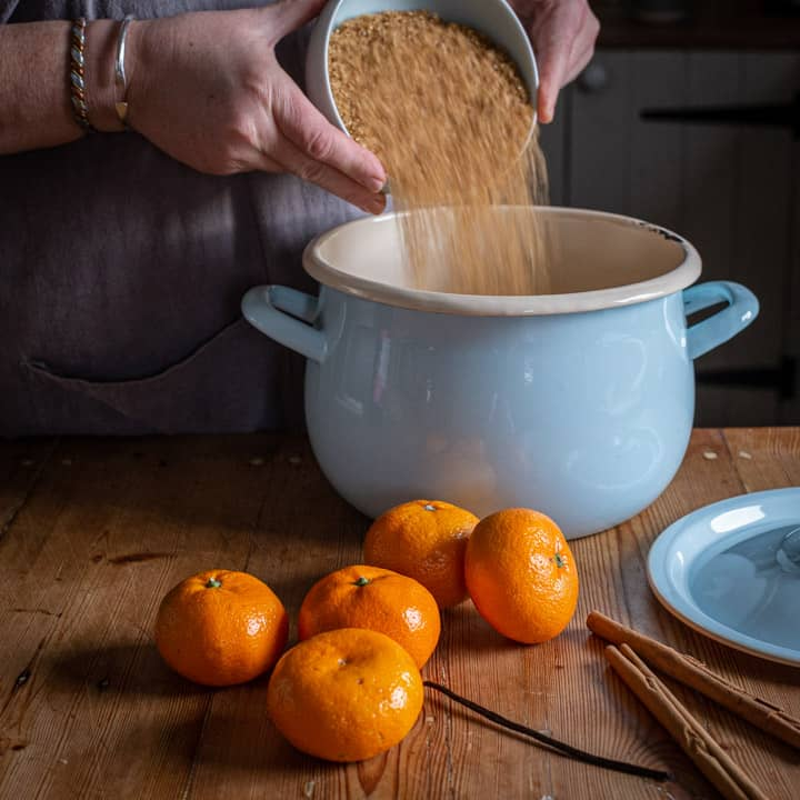 rustic kitchen counter with womans hands pouring a bowl of brown sugar into a pale blue enamel saucepan with satsumas and cinnamon sticks on the counter