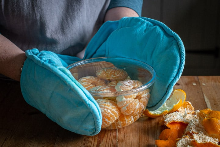 blanched whole satsumas in a glass bowl being held by hands in blue oven gloves