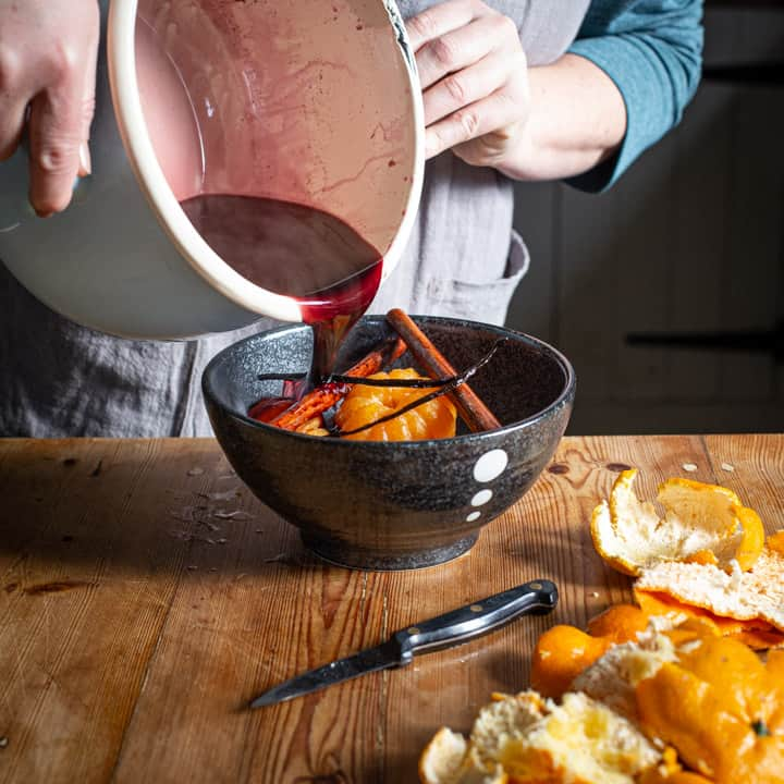 womans hands pouring red wine syrup from a large blue saucepan over a black bowl containing poached whole satsumas on a rustic wooden kitchen counter