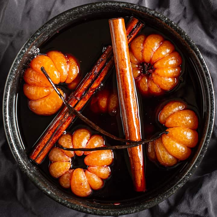 black bowl on grey background with poached satsumas, red wine syrup, cinnamon sticks and a vanilla pod
