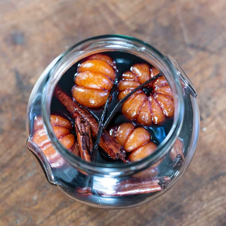large glass jar on wooden background background with whole poached satsumas, red wine syrup, cinnamon sticks and a vanilla pod