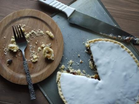 Christmas Mince Pie with icing on it, piece cut out and a wooden plate with a fork and crumbs on it