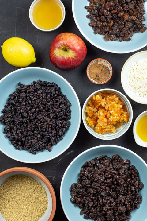 Ingredients in bowls for making best mincemeat recipe including apple, syrup, suet and dried fruits