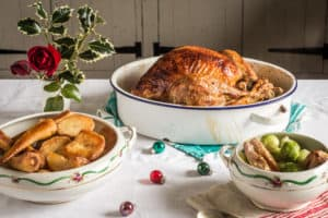 Christmas dinner, including turkey, potatoes, parsnips and brussel sprouts in separate bowls on a table with holly