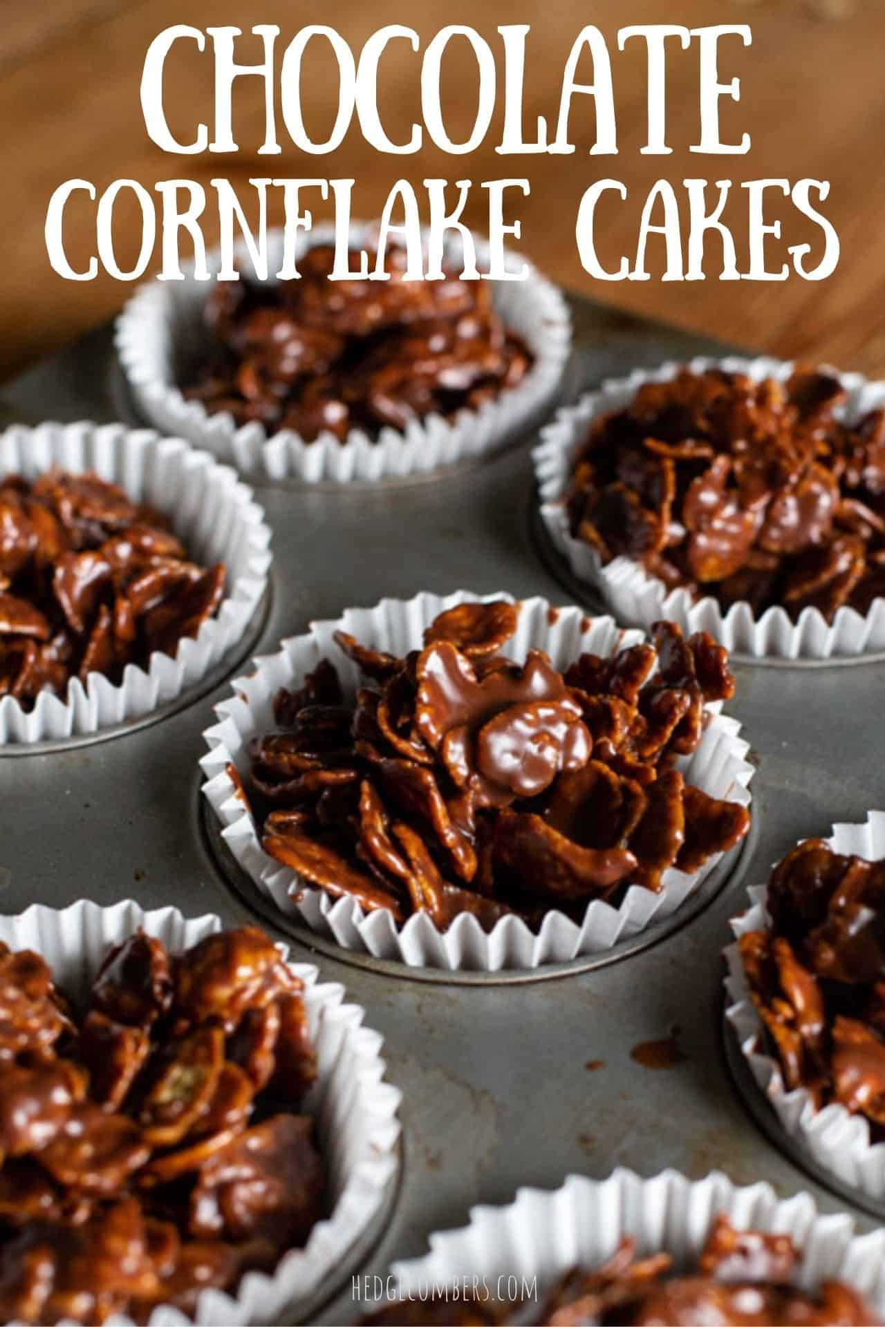 chocolate covered cornflake cakes in white paper cases in a metal baking tray