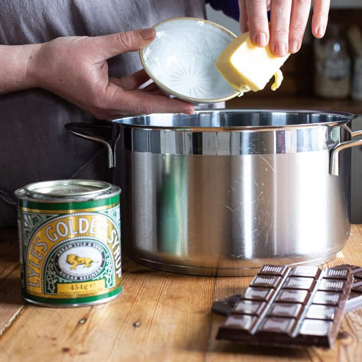womans hands holding a stick of butter over a large silver saucepan on a wooden kitchen counter surrounded by baking mess