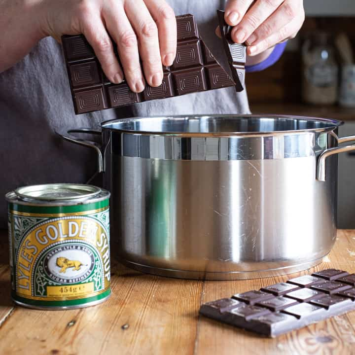 womans hands breaking dark chocolate pieces over a large silver saucepan on a wooden kitchen counter surrounded by baking mess