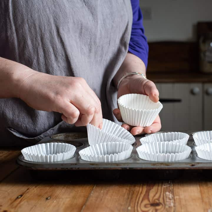 womans hands placing white cupcake cases into a silver cupcake baking tin