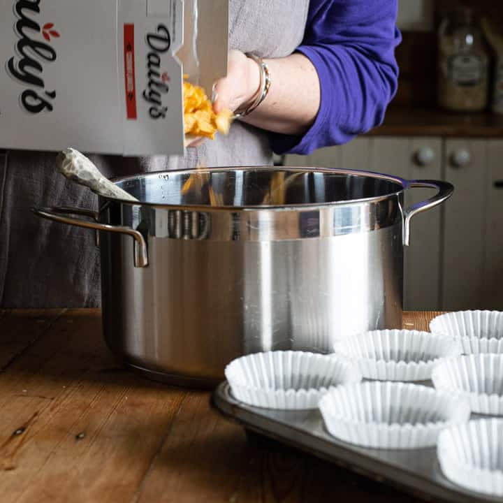 womans hands pouring yellow cornflakes from a white cereal box into a large silver saucepan on a wooden kitchen counter