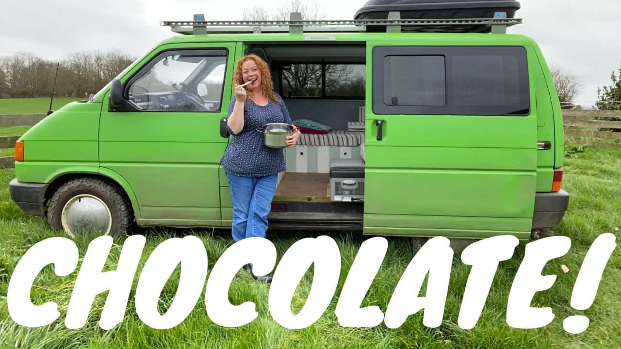 woman with red hair wearing blue clothes stood in front of a bright green campervan licking a a chocolate coated spoon