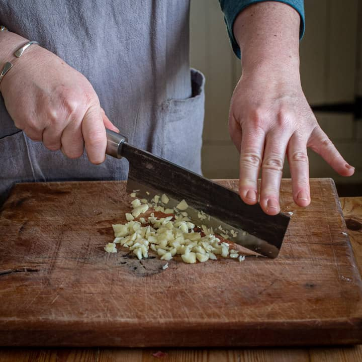 womans hands finely chopping garlic with large Japanese knife on wooden board