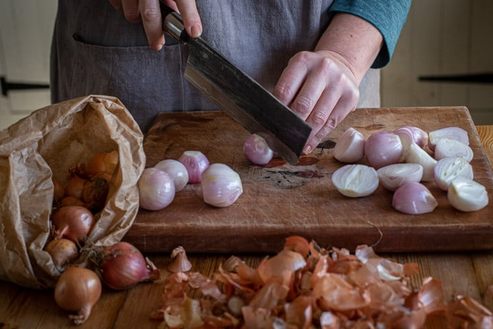 womans hands slicing shallots on a wooden counter